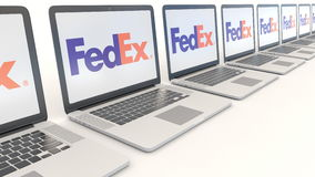 Modern laptops with FedEx logo. Computer technology conceptual editorial 4K clip, seamless loop. Modern laptops with FedEx logo. Computer technology conceptual stock footage