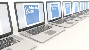 Modern laptops with The Goldman Sachs Group, Inc. logo. Computer technology conceptual editorial 4K clip, seamless loop. Modern laptops with The Goldman Sachs stock video