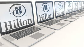 Modern laptops with Hilton Hotels Resorts logo. Computer technology conceptual editorial 3D rendering Royalty Free Stock Image