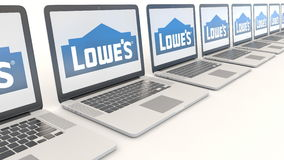 Modern laptops with Lowe`s logo. Computer technology conceptual editorial 4K clip, seamless loop. Modern laptops with Lowe`s logo. Computer technology conceptual stock footage