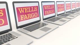 Modern laptops with Wells Fargo logo. Computer technology conceptual editorial 4K clip, seamless loop. Modern laptops with Wells Fargo logo. Computer technology stock footage