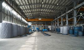 Modern large factory warehouse interior with some goods. Concrete pipes. Industrial production of cement products. Industry manufacturing concept Stock Images