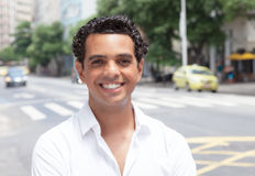 Modern latin guy with toothy smile in the city. With traffic in the background Royalty Free Stock Photography