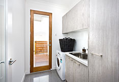 Modern laundry room with grey cupboards on the wall Royalty Free Stock Photos