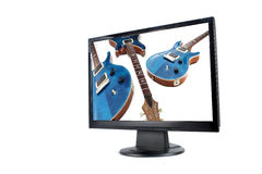 Modern lcd monitor and guitar Stock Images