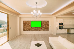 A modern LCD TV with a green screen hanging. On the wall Stock Images