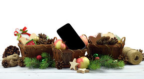 Modern life.Christmas tinsel in a rustic style and  smartphone. Stock Image