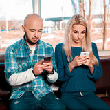 Modern life loving couple passes on mobile phones Royalty Free Stock Photos