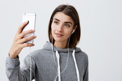 Modern lifestyle. Close up of beautiful young brunette caucasian girl in casual hoodie talking with boyfriend with video Stock Images