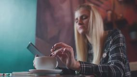 Modern lifestyle: girl with gadget in a coffee shop. Using gadgets. Girl with a haircut lock using a mobile tablet in the coffee shop. Mobile tablet in the stock video footage