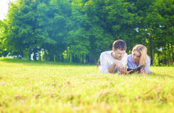 Modern Lifestyle and Ideas: Caucasian Tranquil Couple Lying on G Stock Photography