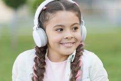 Modern lifestyle. Small child enjoy listening to modern music outdoor. Little girl wearing modern stereo headphones in. Summer. Using modern technology for stock images
