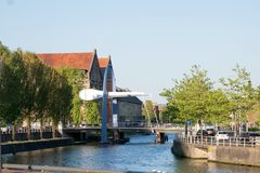 A contemporary bridge structure is seen across a canal in Leeuwarden, Friesland, the Netherlands. A modern lifting bridge crosses a canal in the urban area of royalty free stock photography