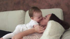 Modern ligger på soffan och kysser förtjusande behandla som ett barn lager videofilmer