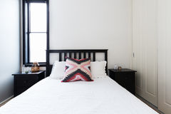 Modern light bright bedroom with shaker bed and white linen Stock Photo