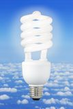 Modern light bulb and climate background. Low-energy light bulb over a blue sky background above the clouds stock image