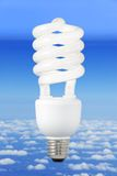 Modern light bulb and climate background. Low-energy light bulb over a blue sky background above the clouds stock photography