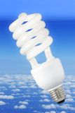 Modern light bulb and climate background. Low-energy light bulb over a blue sky background above the clouds royalty free stock photography