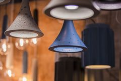 Modern light bulbs in a cafe. Ceiling light fixtures. Chandelier from cement.  Royalty Free Stock Photo