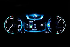 Modern light car mileage on black Fuel economy 25 mph. Modern light car mileage dashboard, milage isolated on a black background. New display of a modern car Royalty Free Stock Image
