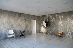 Modern light loft-style room with designer chairs and lighting. Gray walls with the texture of the concrete. Wooden royalty free stock images