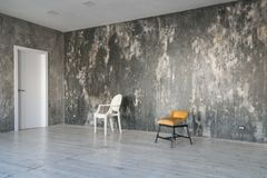 Modern light loft-style room with designer chairs and lighting. Gray walls with the texture of the concrete. Wooden stock photos