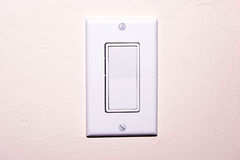 Modern light switch. Modren light switch with white cover plate on textured wall Stock Photo