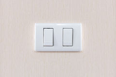 Modern light switch on a creamy wallpaper Stock Photos