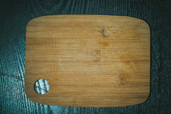 Modern light wooden cutting board with ring hole on a black tabl Royalty Free Stock Photo