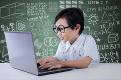 Modern little girl using laptop in classroom Royalty Free Stock Images