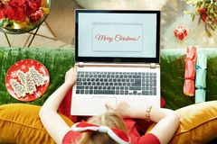 Modern little princess writing Merry Christmas email on laptop