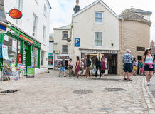 Modern living in historic English village. Mevigissey, England - July 25, 2013: People milling about on cobbled towns street and lane modern living in typical stock photos