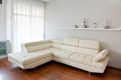 Modern living room. With white sofa, wooden floor and golf trophy on the rack Royalty Free Stock Images