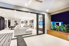 Modern living room is attached to the patio area. From the outside through the glass door Stock Photos