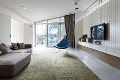 Modern living room with blutterfly angled roofline and wall hung. Cabinets and shelf Royalty Free Stock Image