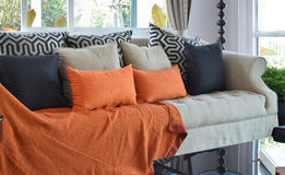 Modern living room with brown and orange sofa and pillows. Modern living room design with brown and orange tweed sofa and black pillows Royalty Free Stock Images