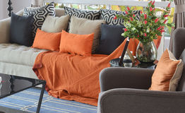 Modern living room with brown and orange tweed sofa. Modern living room design with brown and orange tweed sofa and black pillows Royalty Free Stock Photos