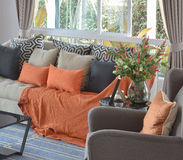 Modern living room with brown and orange tweed sofa. Modern living room design with brown and orange tweed sofa and black pillows Stock Photo