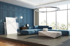 Blue panoramic living room corner poster. Modern living room corner with blue walls, a concrete floor, a blue sofa and an original coffee table. A poster and a Royalty Free Stock Photography
