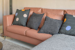 Modern living room design with brown leather sofa and black pillows Royalty Free Stock Images