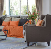 Modern living room design with brown and orange sofa and black pillows. Modern living room design with brown and orange tweed sofa and black pillows Stock Images