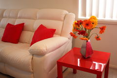 Modern living room detail. Interior design of a modern living room with a white leather sofa and flowers on the red side table Royalty Free Stock Image