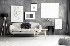Modern living room interior. With bright sofa, wooden table and posters hanging on a textured wall Royalty Free Stock Photo