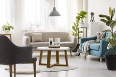 Modern living room interior. Gray lamp above white round table in modern living room interior with turquoise armchair next to beige sofa Stock Photography