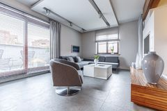 Modern living room interior. Grey armchair next to white table in modern living room interior with vase on cupboard and windows Stock Photography