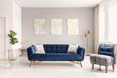 A modern living room interior of a luxurious hotel apartment with a designer couch, an armchair and art decorations. Real photo. Concept royalty free stock photography
