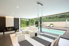Modern living room overlooking the garden and swimming pool. Nobody inside royalty free stock photo