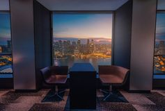 Modern living room with view Singapore skyline at sunset royalty free stock photography