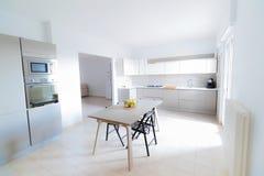 Modern, ljus, ren, kökinre med rostfritt stålanordningar och friutäpple på tabellen i ett lyxigt hus fotografering för bildbyråer