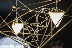 Modern ljuskrona i form av en triangel och metalliska geometriska former, på en svart bakgrund Royaltyfri Fotografi
